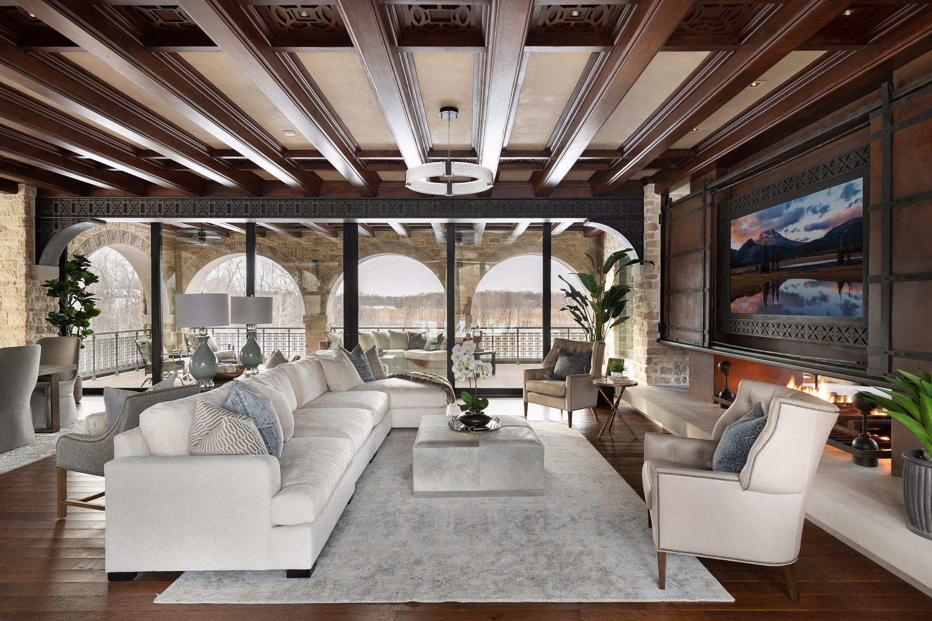 The great room features a custom designed entertainment center with fireplace and walls of glass opening to two stone arched terraces.