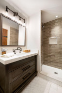 The third bedroom features this ensuite bathroom with Carrara marble countertop, custom designed lighting and faucet, and designer tile shower surround.