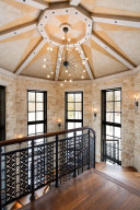 The design in the iron railing is duplicated throughout the home both inside and out. Beautiful windows grace the turret-style staircase