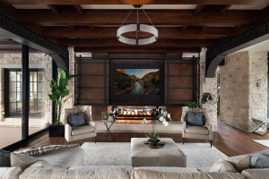 The great room features the uniquely designed fireplace and the wall of glass opens to the arched stone terrace.