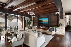 An incredible statement piece, the massive steel fireplace and media doors operate by a pulley and chain crank to reveal a high-tech television.