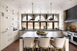 The kitchen looks out over a trio of aches that frame the views of the surrounding woods.