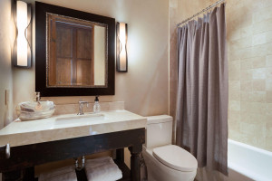 The guest bedroom features this ensuite bathroom with granite countertop and designer tile tub surround.
