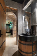 The lower level three-quarter bathroom features a wine barrel inspired vanity, shower and sauna.