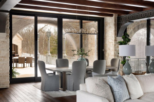 The dining room overlooks the stone arched terrace and outdoor dining area with stacked stone grill.