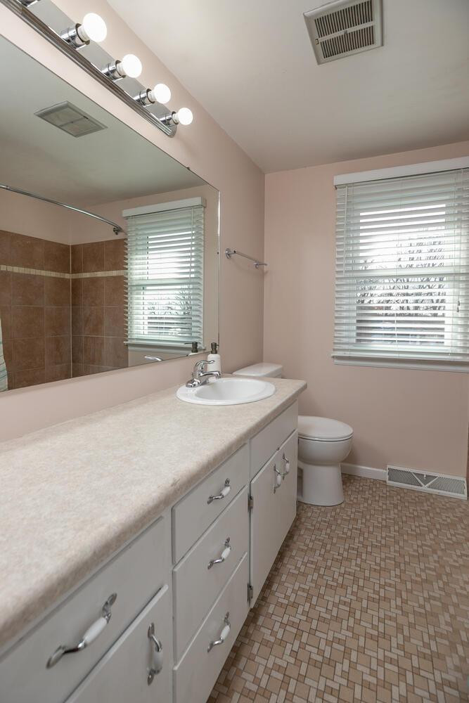 upper level full bath with file flooring and tile shower