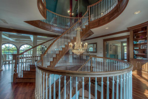 Spiral staircase showcases a crystal chandelier.