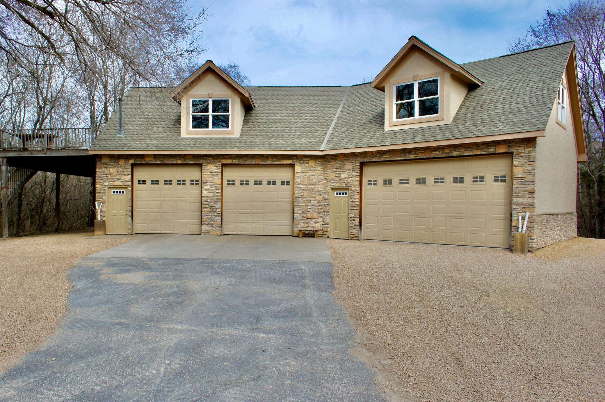 The Garage Mahal that will be the envy of all your friends & family 2000 square feet on the main level. Each of the overhead doors are 10' tall! See the 15'x28' carport w/deck above and there's another rear covered storage as well.