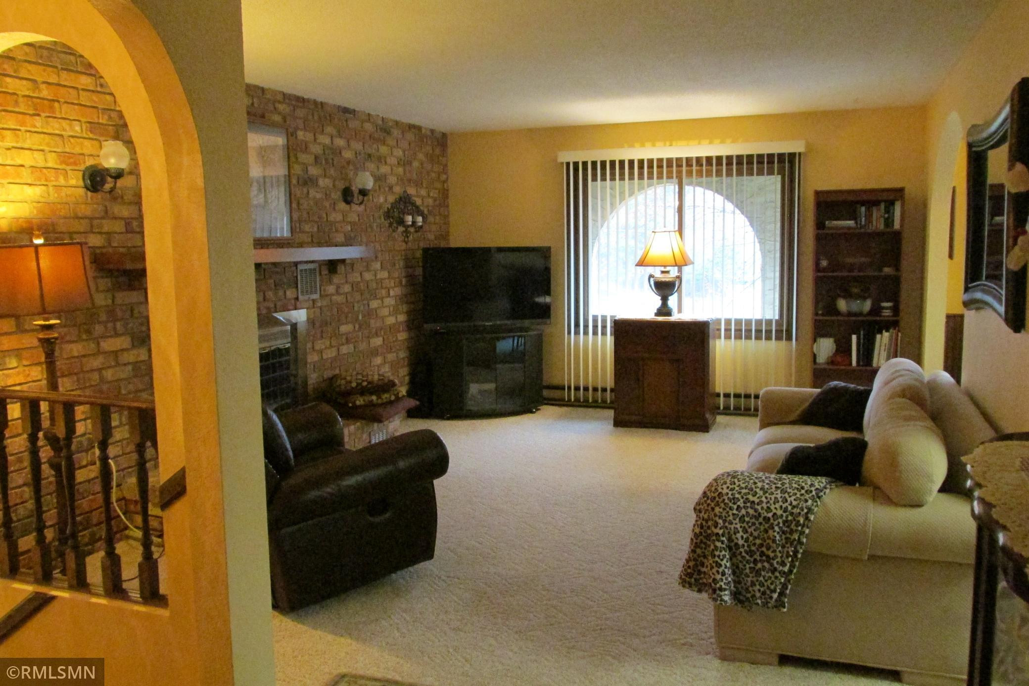Inviting living room with full wall brick fireplace.