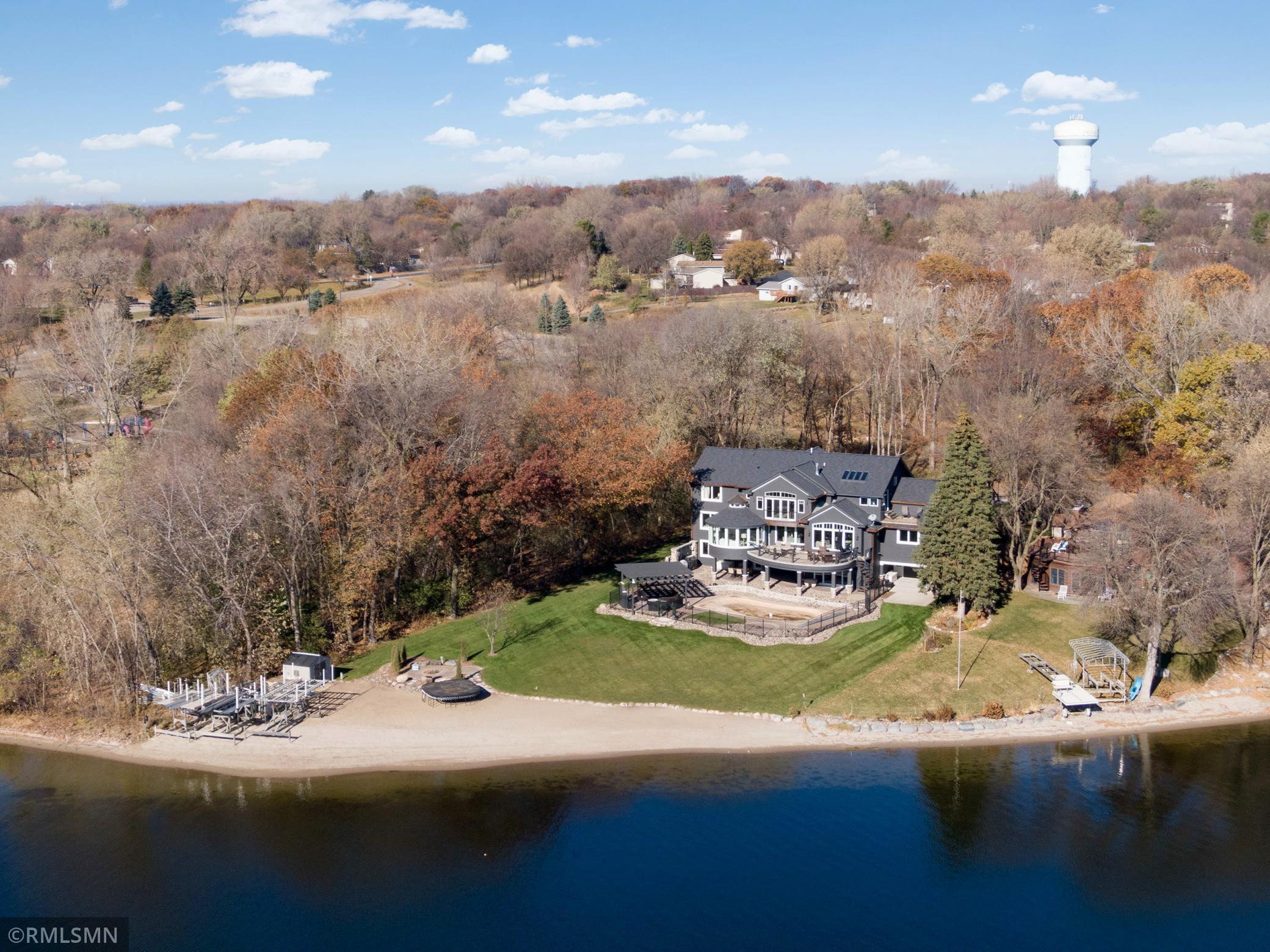 This pristine Prior Lake home is nestled in a private wooded atmosphere, directly next to Sand Point Beach Park and close to everything that matters.