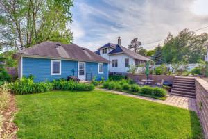 Beautiful backyard with paver walk leading to large detached garage