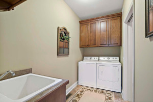 walk-thru laundry room with utility tub, extra storage - and pocket door for privacy