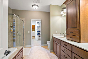Master Bath with separate tub and shower, extra cabinet space and walks through to closet and laundry room