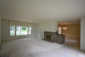 Large living room with wood-burning fireplace and is adjacent to the dining room.