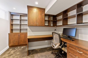 Basement home office with custom built-in desk and cabinets.
