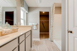 Connected to the primary suite is this bathroom, which includes a double-vanity, stand-in shower and serves as the passage way to the bedrooms oversized walk-in closet!! (Photos of the same floorplan, colors are similar)