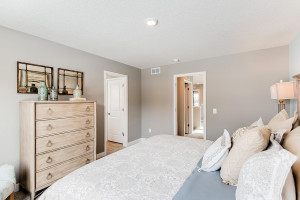 A second view of the Primary Suite, seen here with a King sized bed and the access point to the room's Primary bathroom!! (Photo of same plan, colors are similar)