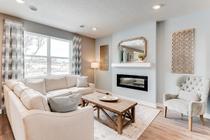 Soaring windows shed light on a main level living space that is large enough to handle most furniture set-ups and features a contemporary electric fireplace and mantle combination! (Photos of the same floorplan, colors are similar)