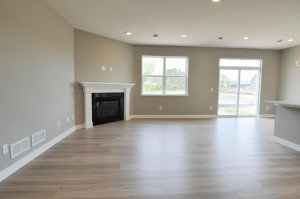 The main level also features this family room, which is large enough to accommodate just about any furniture configuration and is highlighted by a corner gas fireplace! (Photo of same plan, colors are similar)