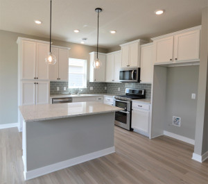 The centerpiece of the space is the island - which has cabinet storage and a recycling center on one side, and an overhang for seating/dining on the other! (Photo of same plan, colors are similar)