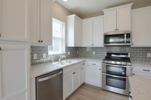 Stunning AND functional all in one, as the kitchen space features a pantry cabinet for help with storage, countertops coated in Quartz and a glass tile backsplash the perfect touch of color! (Photo of same plan, colors are similar)