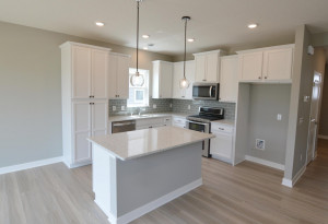 A kitchen built to perform - complete with an island, pantry closet, stainless appliance package including a vented microhood and double-oven gas range! (Photo of same plan, colors are similar)