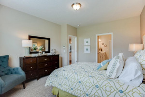 Another view of the primary suite, and the access point to the primary suite bath - which is loaded with amenities and connects directly to a massive walk-in closet! *Photo of previous model, selections will vary.