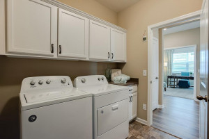 Another feature in the home is this main level laundry room, complete with cabinets! *Photo of previous model, selections will vary.