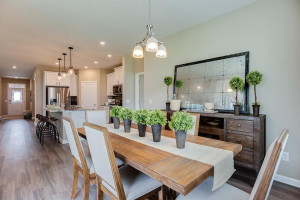 Grab a meal at the island, or utilize this dining space - which features soaring windows allowing plenty of natural light to stream into the space and overlooks the home's deck! *Photo of previous model, selections will vary.