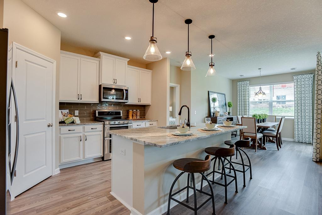 An elegant combination of quartz countertops and while enameled maple cabinets help bring to life a kitchen that will prove to be every bit as functional as it is beautiful. *Photo of previous model, selections will vary.