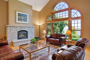 The vaulted great room features an oversized window that looks out to the lake.