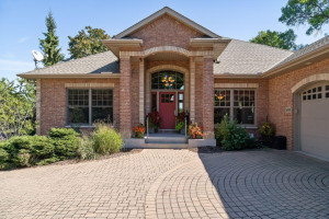 The beautiful paver driveway leads up the inviting front door.