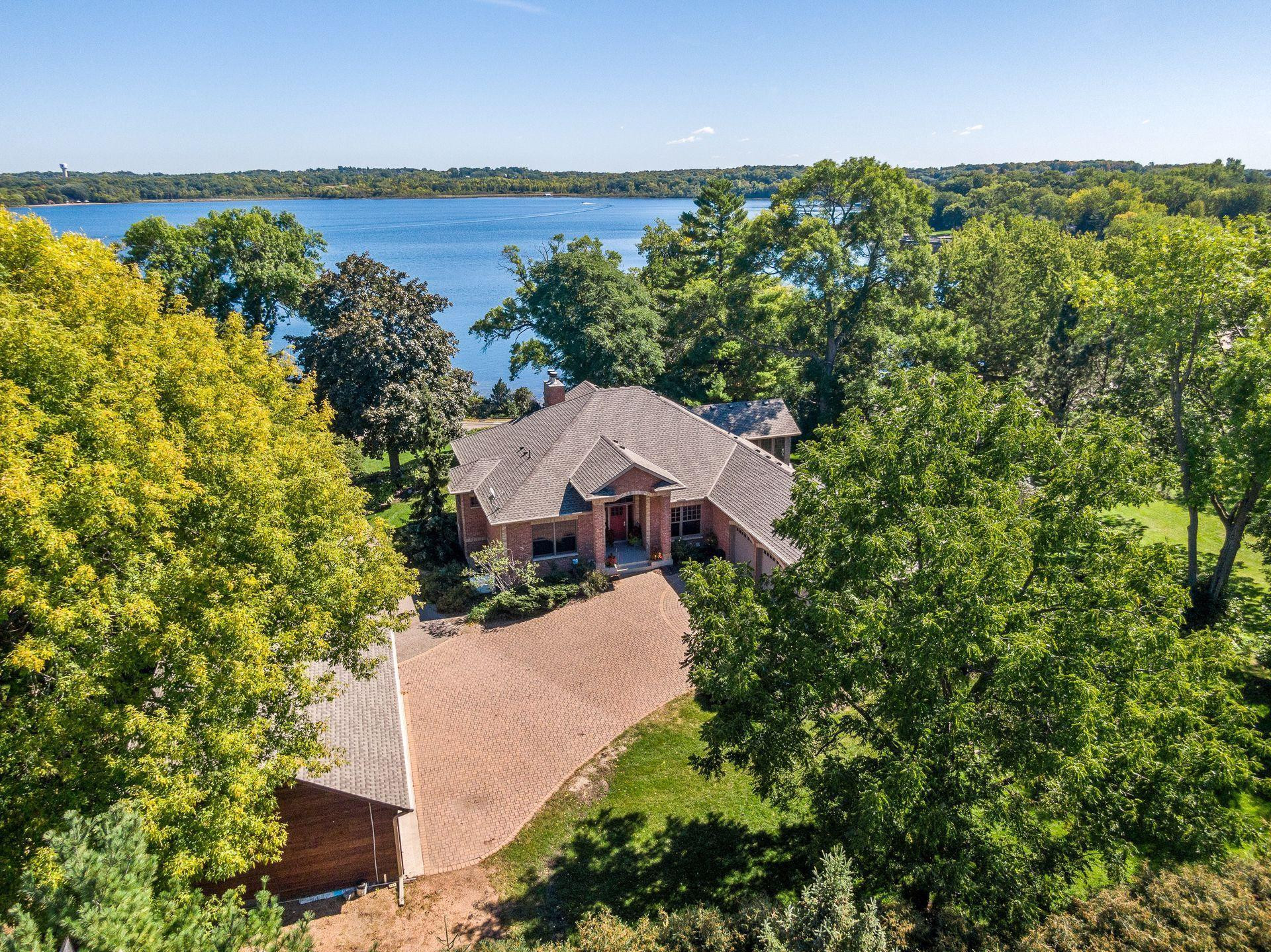 Surrounded by mature trees and nestled on a private lot, this custom built home is a stunning in-town retreat on the shores of Lake Minnewashta.