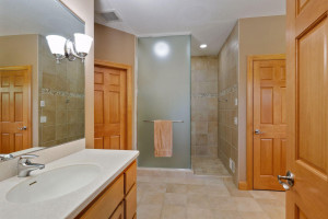 The spacious walk-in shower is fully tiled and offers a frosted glass enclosure. Two walk-in closets complete the master suite.