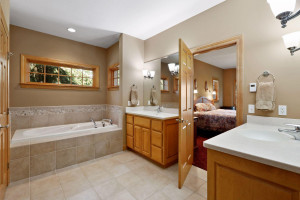 A private spa, the master bathroom features heated tile floors, separate comfort-height vanities and a large jetted bathtub.