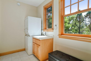 The main level laundry room was designed with a stacking washer and dryer and features additional space for a craft room or sewing space.