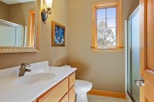 Just off the mud room is a 3/4 guest bathroom with an elevated vanity, designer mirror and tiled flooring.
