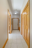 There is ample storage in this mud room which features two coat closets, a broom closet and built-in boot bench.