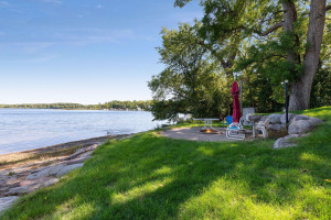 Professionally landscaped, the shoreline features a sandy beach and paver patio wit ha campfire ring.