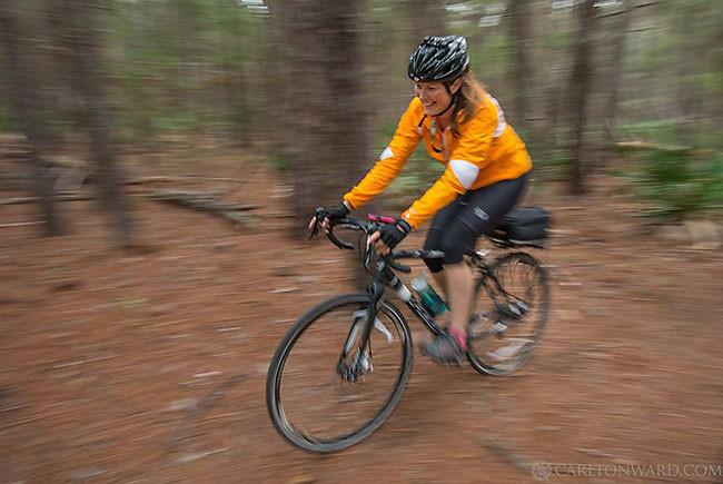 Mallory Dimmitt biking though pine
