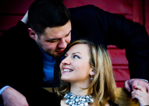 engaged couple on bench in front of red wall