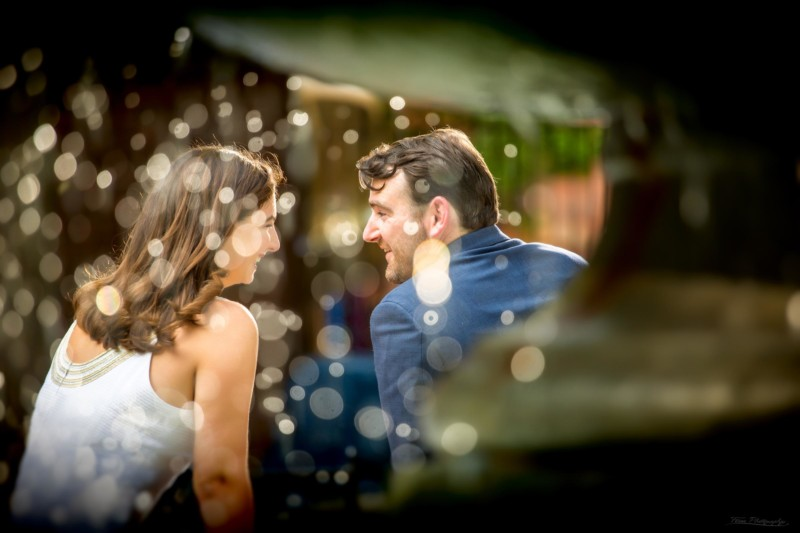 couple photographed through water falling in fountain during engagement shoot in Boston