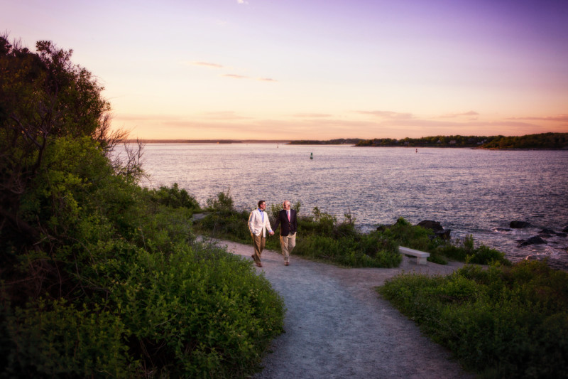 2 gay men walk hand in had for engagement pictures in maine