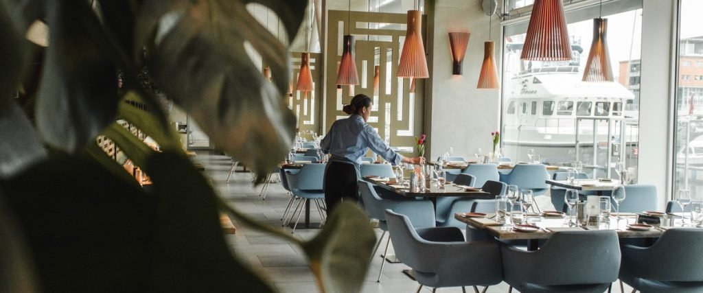 woman setting tables in an empty restaurant
