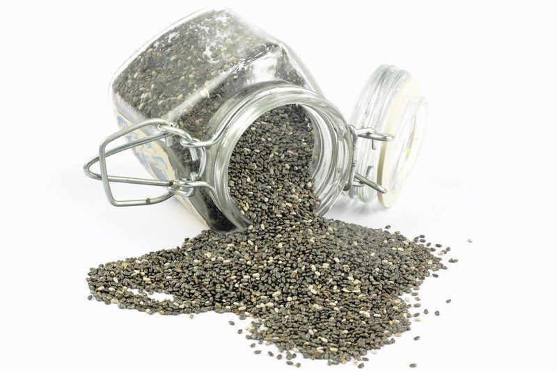 Chia seeds spilling from a glass jar