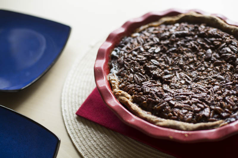 finished pecan pie in red dish with two blue plates
