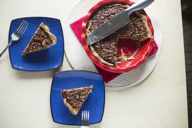 Two slices of pecan pie on plates and whole pecan pie on side
