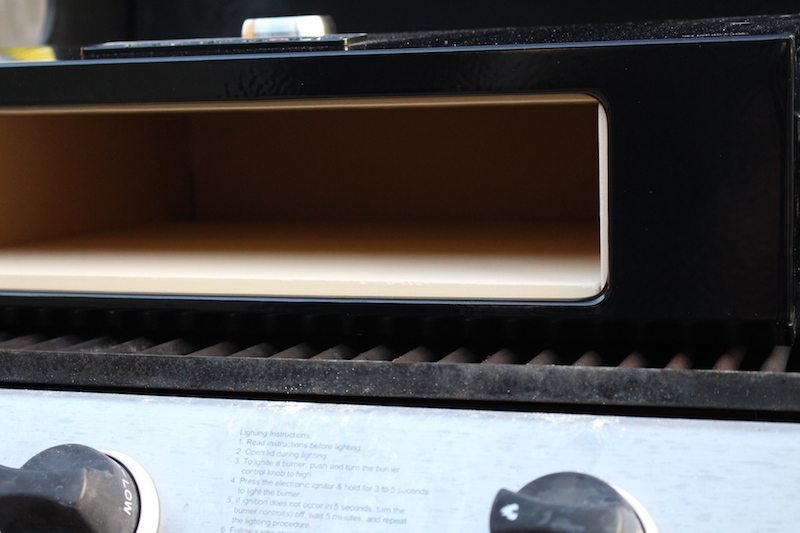 inside closeup image of clean bakerstone pizza box on top of gas grill