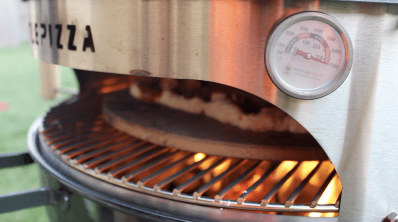 kettlepizza charcoal grill cooking pizza at over 700 degrees fahrenheit shown on temperature gauge