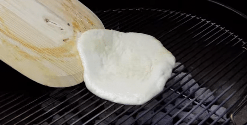 placing raw pizza dough with olive oil on a charcoal grill